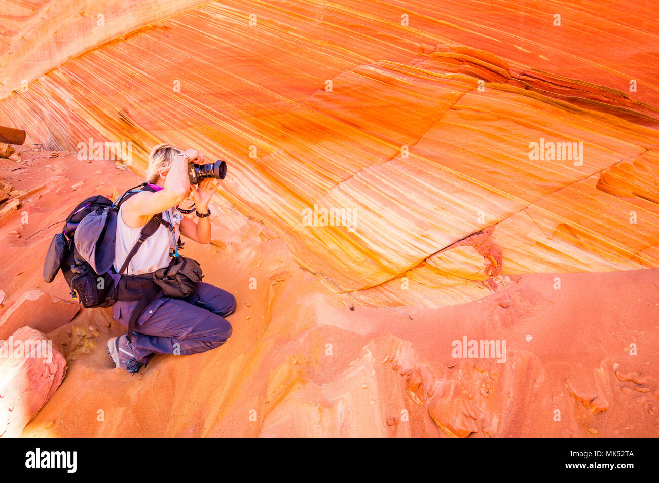 Female photographer with day pack surrounded by red and gold striped sandstone South Coyote Buttes Vermilion Cliffs National Monument, Arizona. - Stock Image