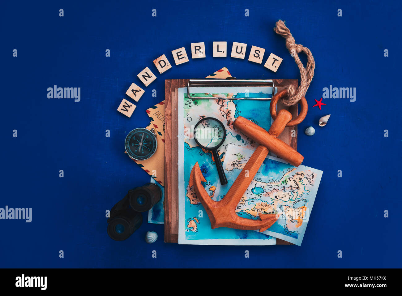 Travel and exploration concept with watercolor maps, compass, wooden anchor, binoculars, magnifying glass and Wanderlust scrabble letters. Vacation flat lay on a navy blue background with copy space - Stock Image