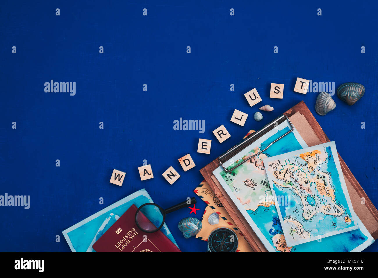 Sea travel and exploration concept. Watercolor maps, passport, compass, binoculars, envelopes, magnifying glass, and Wanderlust scrabble letters flat lay on a navy blue background with copy space - Stock Image