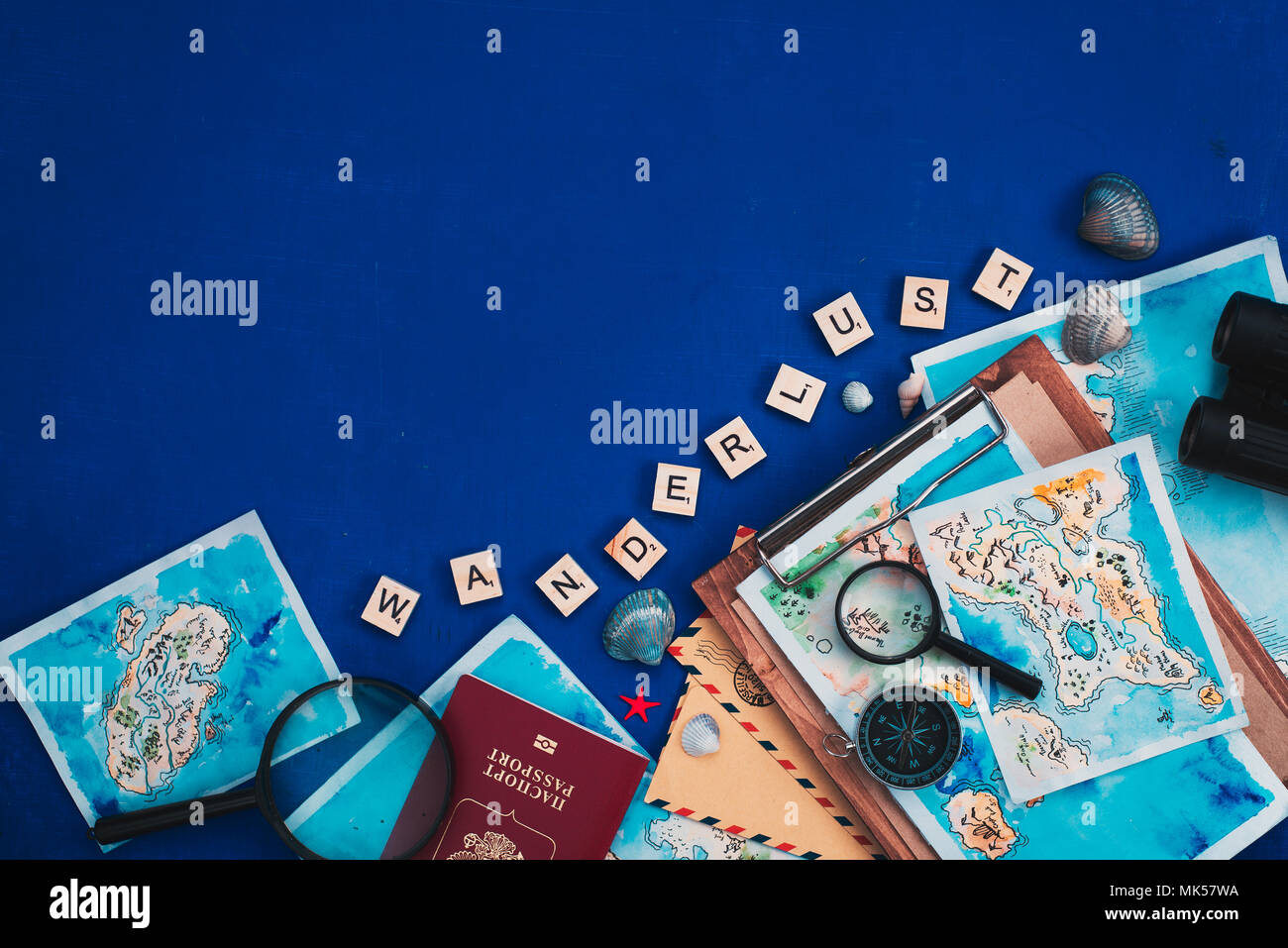 Header with travel and exploration concept. Watercolor maps, passport, compass, binoculars, envelopes, and Wanderlust scrabble letters flat lay on a navy blue background with copy space - Stock Image