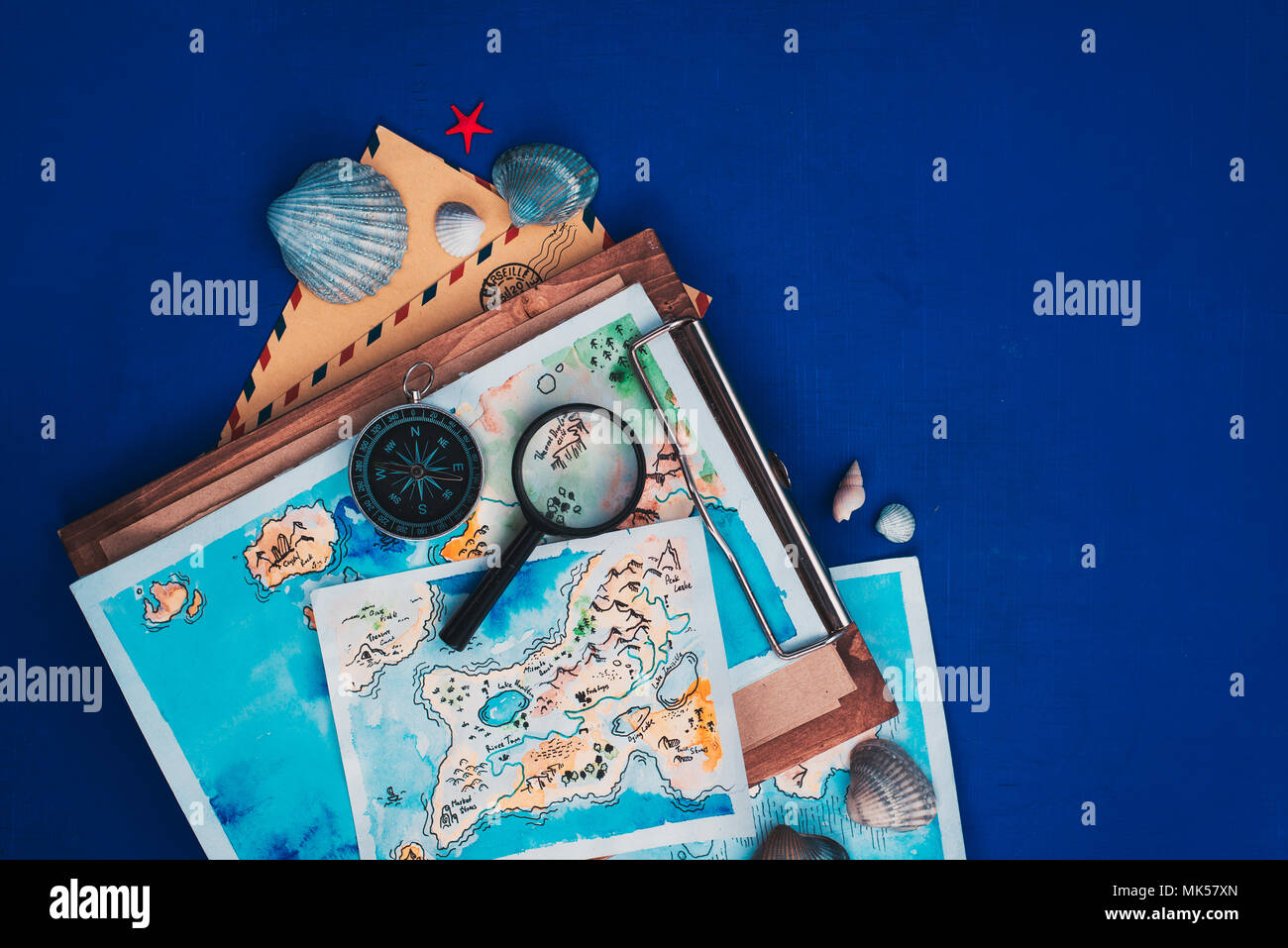Header with sea travel and exploration concept. Watercolor maps on a wooden clipboard, compass and magnifying glass flat lay on a marine blue background with copy space - Stock Image