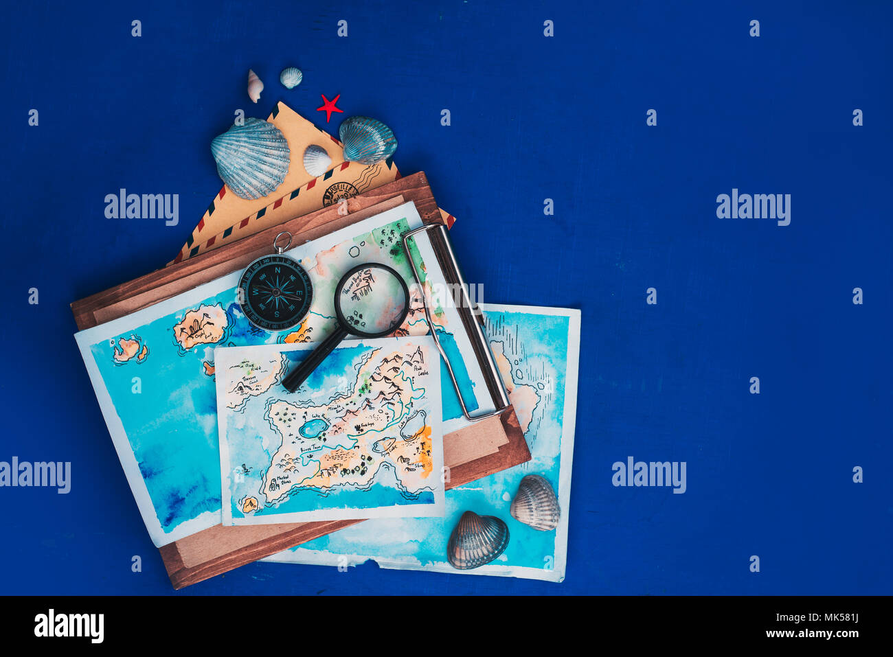 Sea travel and exploration concept. Watercolor maps on a wooden clipboard, compass and magnifying glass flat lay on a navy blue background with copy space - Stock Image