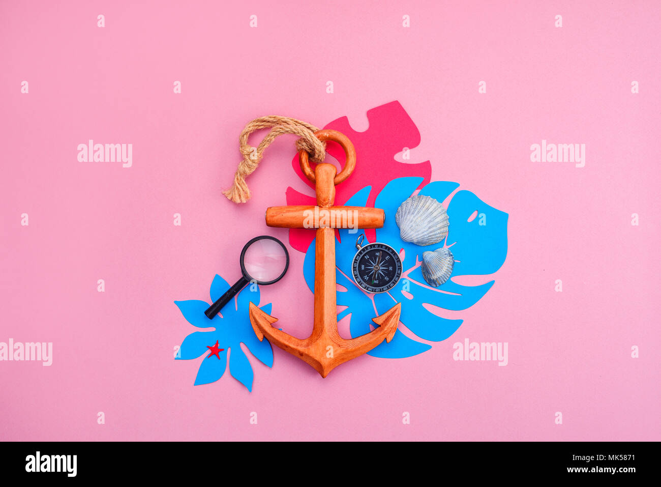 Colorful travel and vacation concept on a bright pink background. Tropical leaves, wooden anchor, compass and sea shells with copy space. - Stock Image