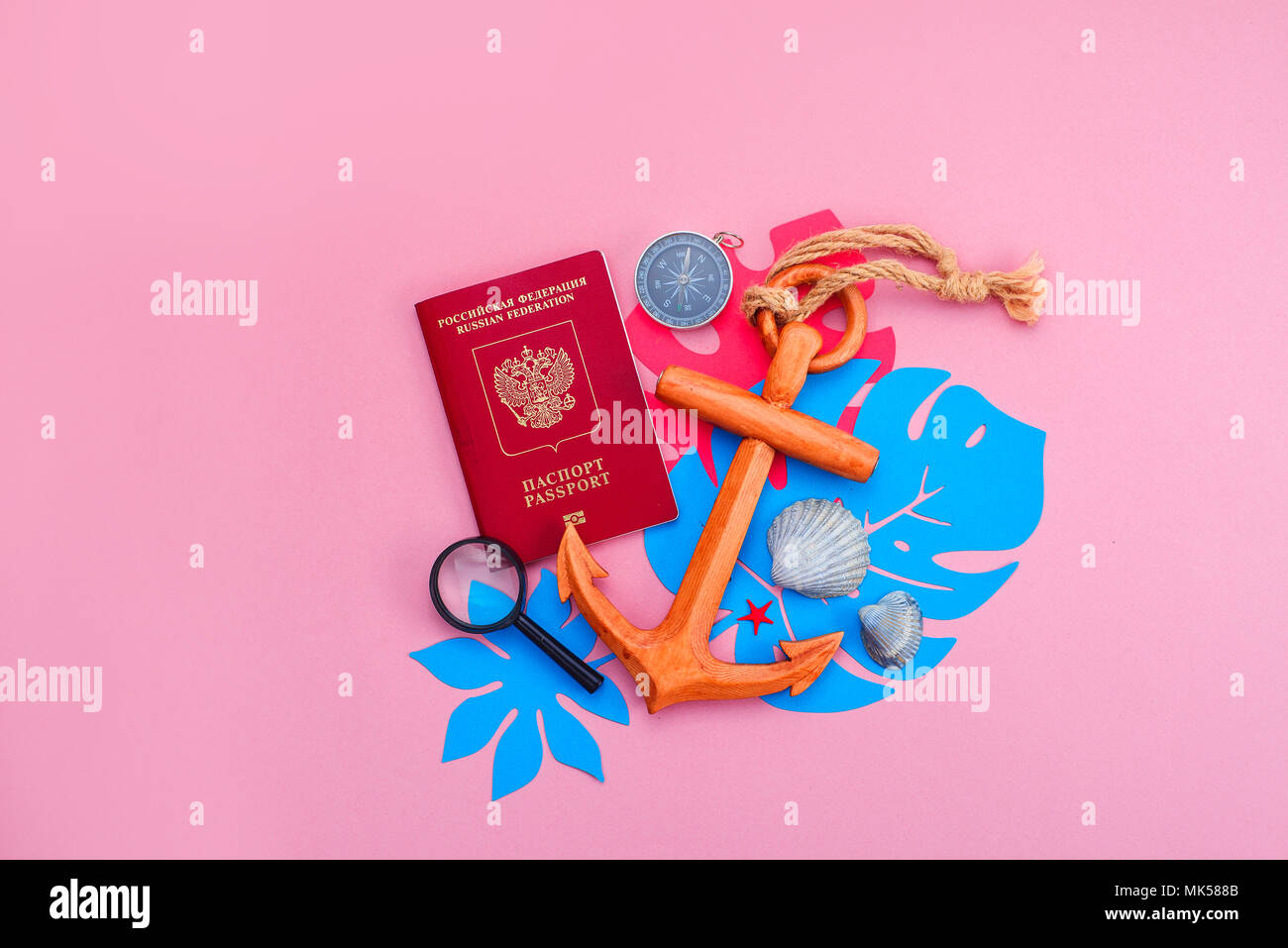 Colorful travel and vacation concept on a bright pink background. Tropical leaves, wooden anchor, passport, compass and seashells with copy space. - Stock Image