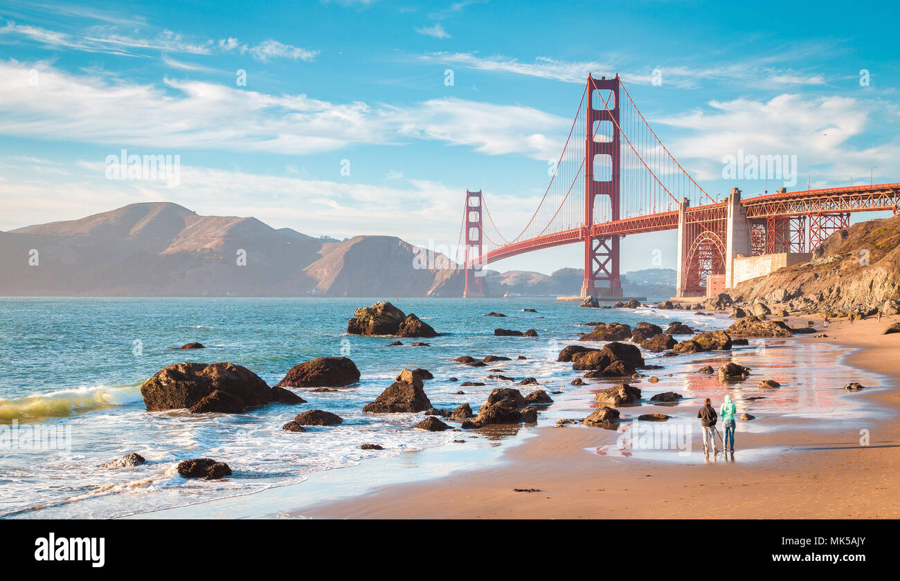 Classic panoramic view of famous Golden Gate Bridge seen from scenic Baker Beach in beautiful golden evening light on a sunny day with blue sky and cl Stock Photo