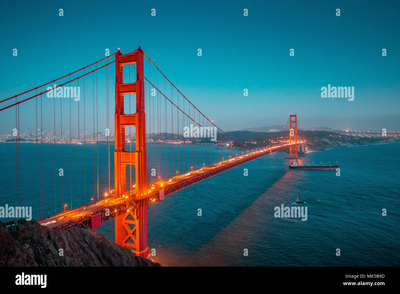 Classic panoramic view of famous Golden Gate with cargo freight ship in beautiful post sunset twilight during blue hour at dusk in summer, San Francis - Stock Image