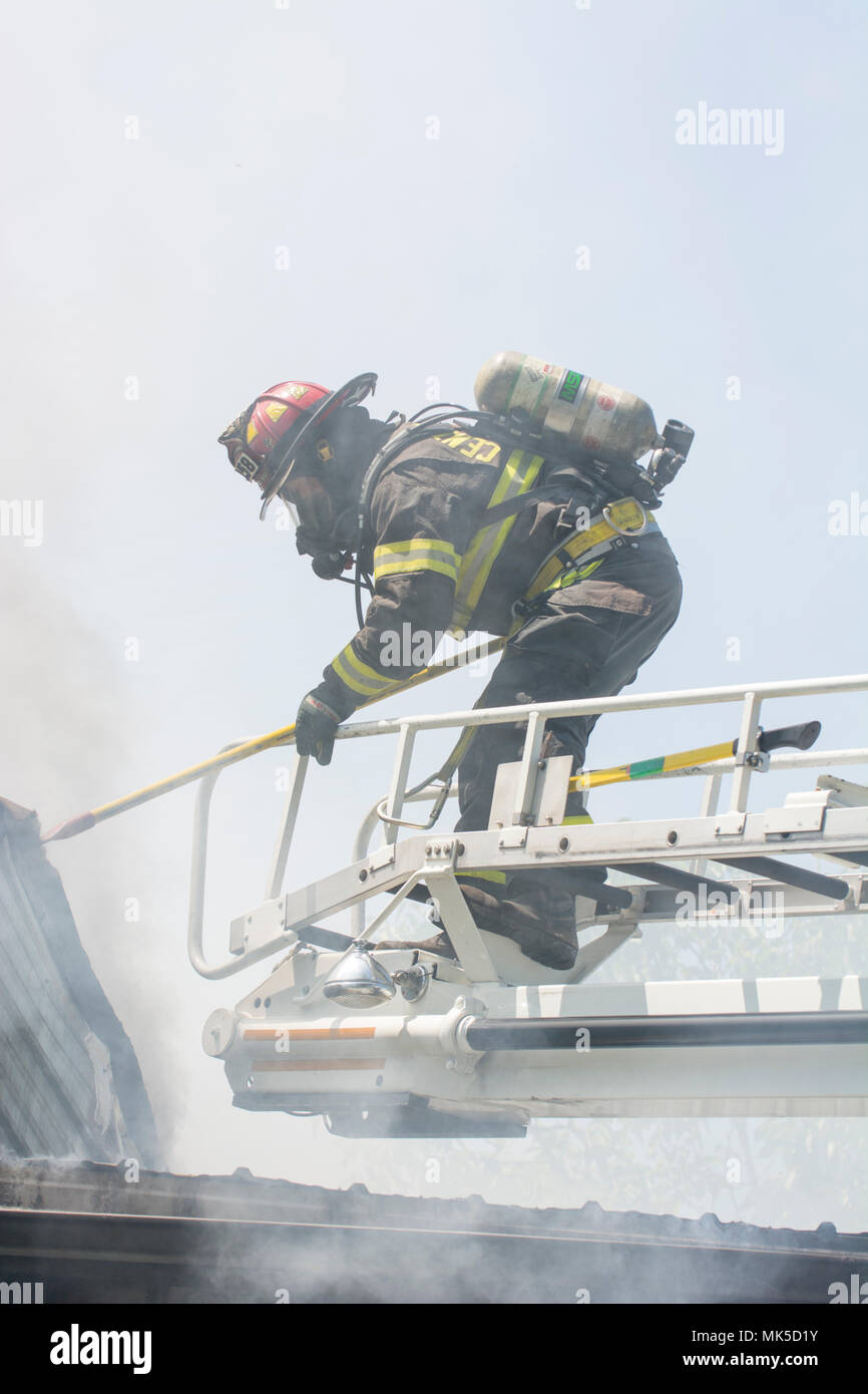 A firefighter stands on a truck ladder over a roof wiht a tool. He is taking apart a smoldering roof to look for hot spots to put out. - Stock Image