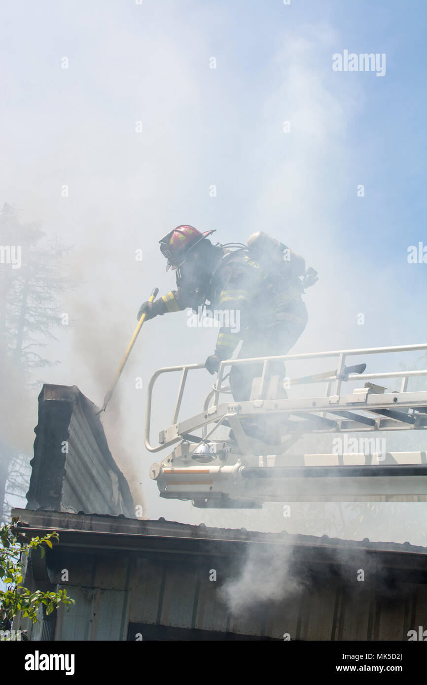 A firefighter stands on a truck ladder over a roof wiht a tool. He is taking apart a smoldering roof to look for hot spots to put out. Stock Photo