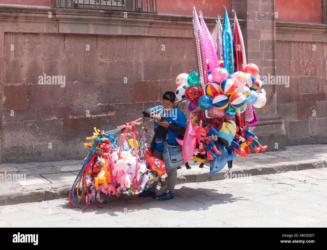 In San Miguel de Allende, a ballon seller looking at his cellphone - Stock Image