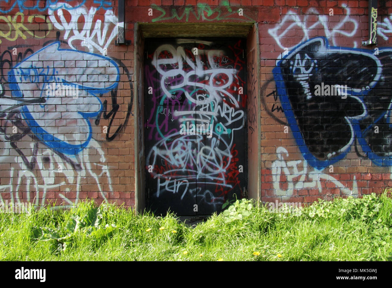 Locked and Closed Door on London Canal Towpath, covered in Tag Graffiti - Stock Image