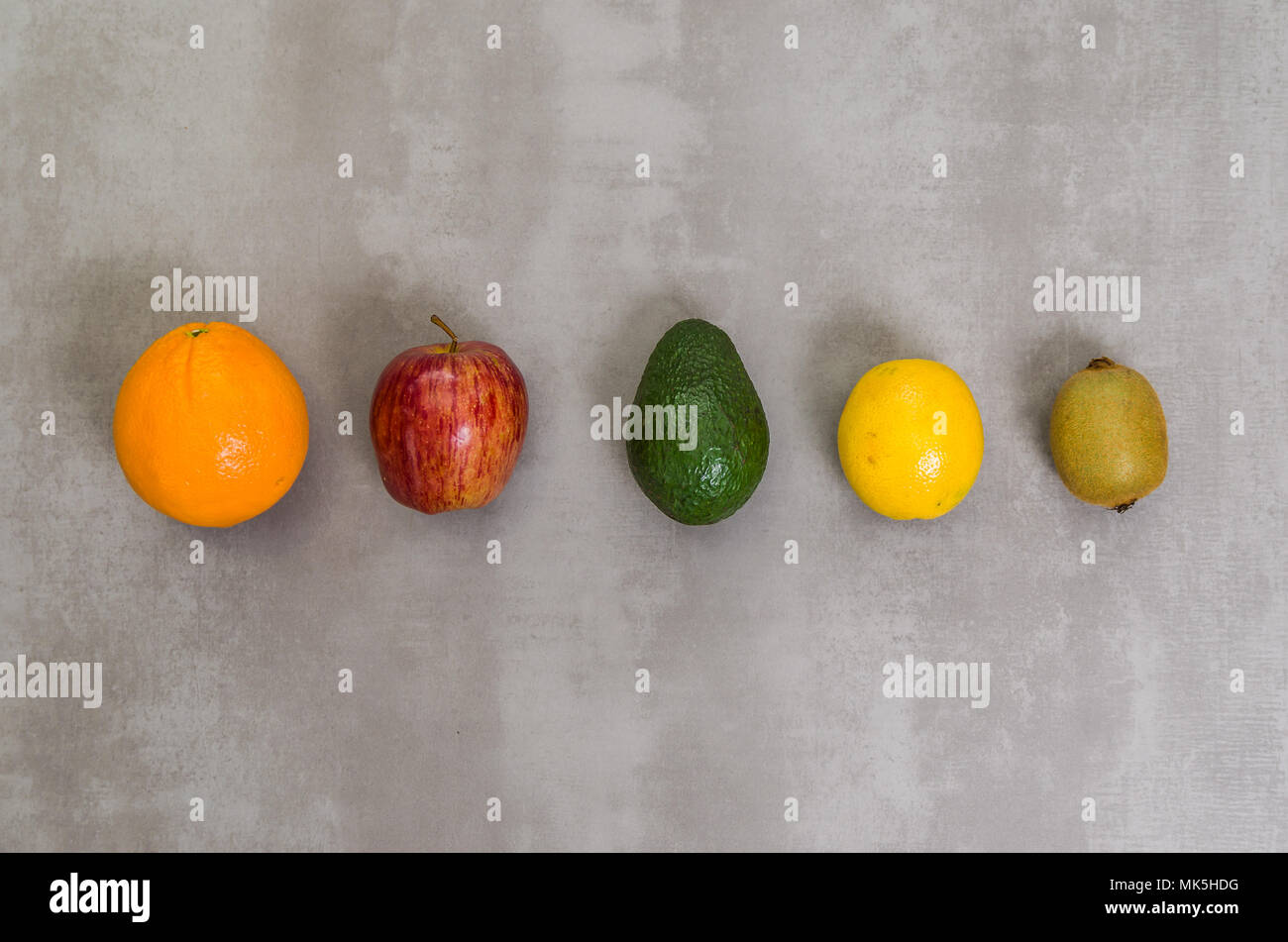 Great concept of healthy eating, various fruits on gray background, polished concrete. Orange, apple, kiwi, lemon. Stock Photo