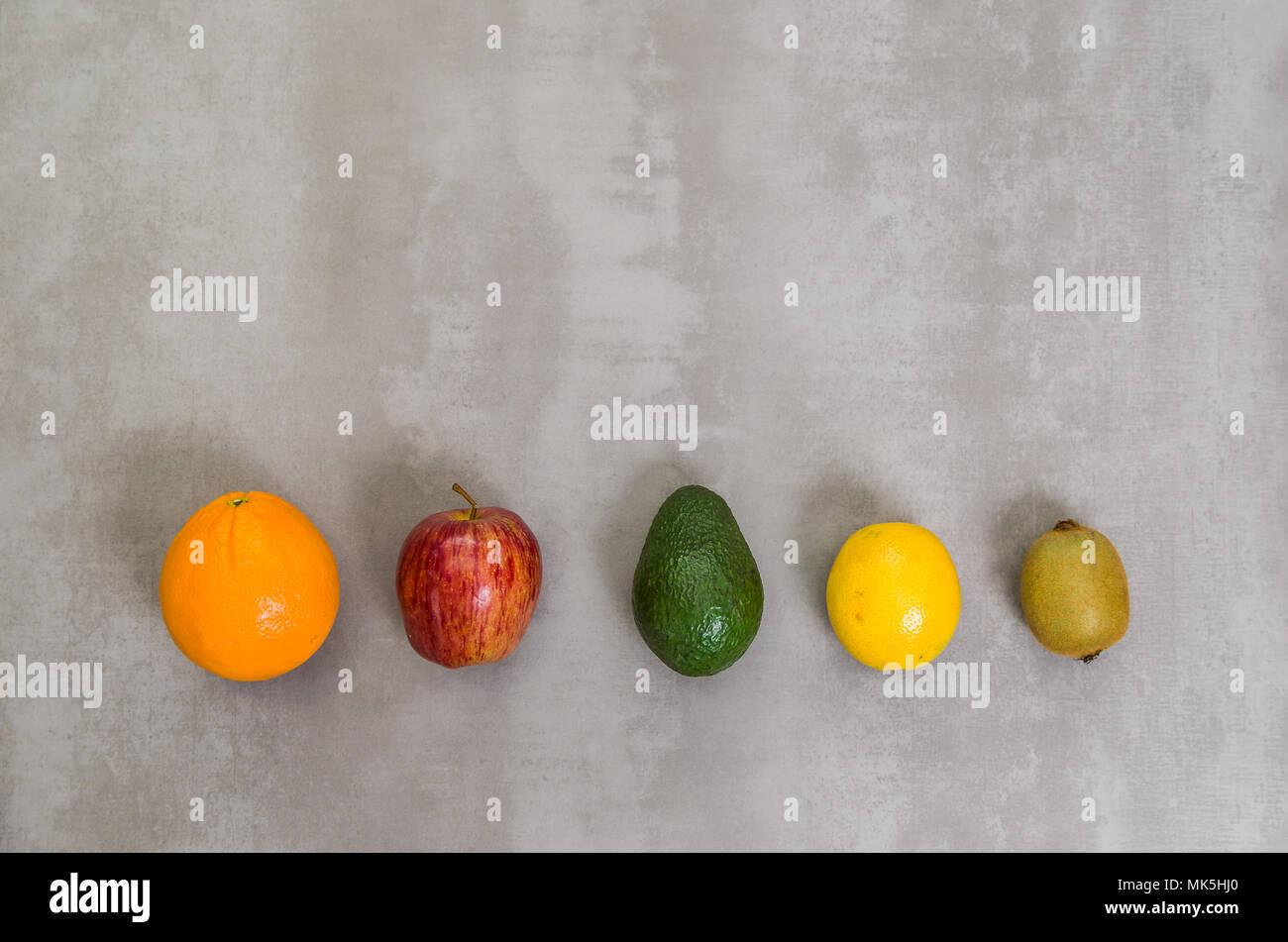 Great concept of healthy eating, various fruits on gray background, polished concrete. Orange, apple, kiwi, lemon. - Stock Image