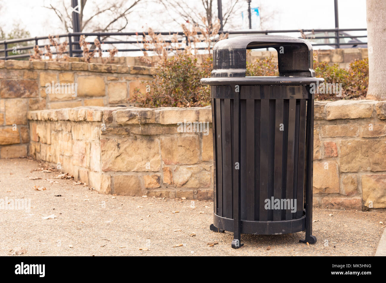 trash can in park alongside stone brick wall on gravel walkway - Stock Image