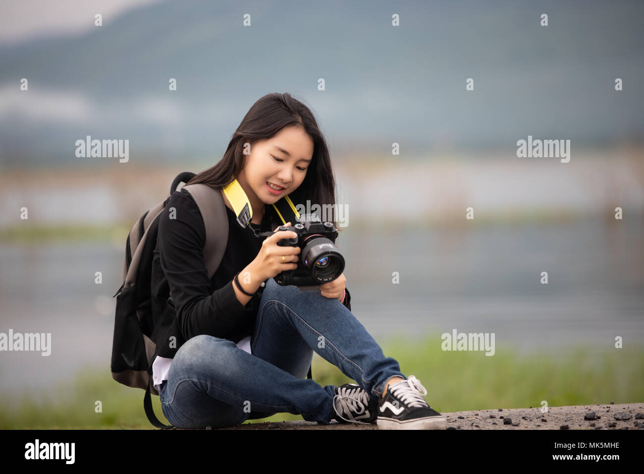 sian  young women people Hiking with friends backpacks walking together and looking map and taking photo camera by the road and looking happy ,Relax t - Stock Image