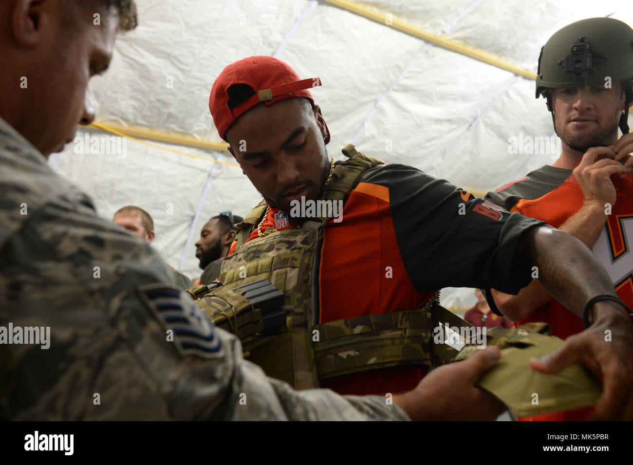 U.S. Air Force Tech. Sgt. Brian Jones, assistant security forces flight chief for U.S. Special Operations Command Deployment Cell, helps Tampa Bay Buccaneers wide receiver DeSean Jackson and third-string quarterback Ryan Griffin try on tactical gear during their visit to MacDill Air Force Base in Tampa, Fla., Nov. 7, 2017. The football players and cheerleaders toured USSOCOM and other base facilities to meet with currently serving personnel and to experience a glimpse of military life. (Photo by U.S. Air Force Master Sgt. Barry Loo) Stock Photo