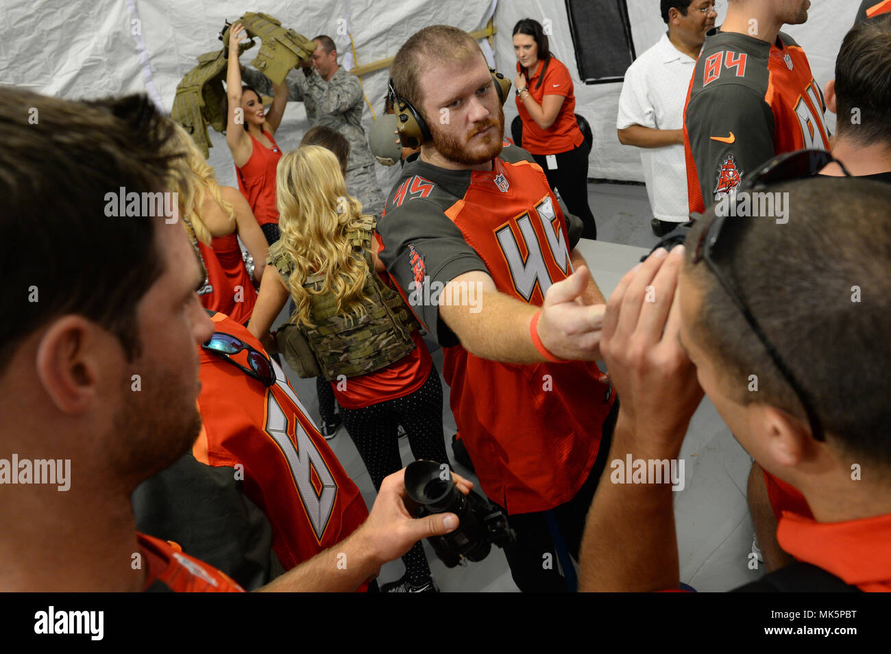 The Tampa Bay Buccaneers try on tactical gear with U.S. Special Operations Command Deployment Cell personnel on MacDill Air Force Base in Tampa, Fla., Nov. 7, 2017. The football players and cheerleaders toured USSOCOM and other base facilities to meet with currently serving personnel and to experience a glimpse of military life. (Photo by U.S. Air Force Master Sgt. Barry Loo) Stock Photo