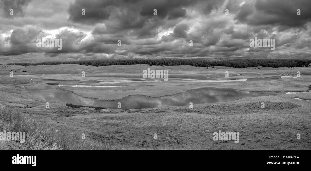Storm clouds gather as a thunderstorm forms over a river, black and white image. - Stock Image