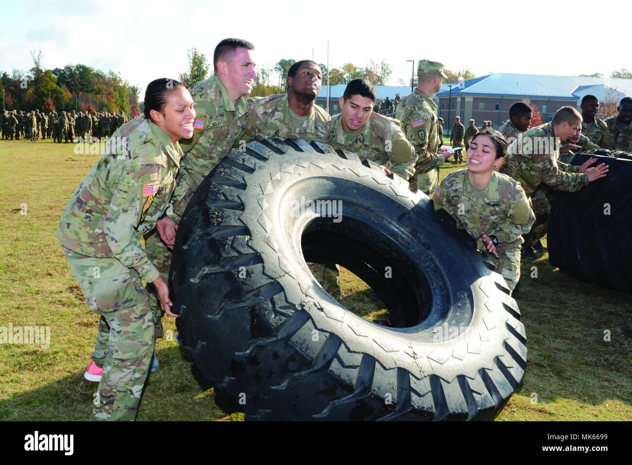 Soldiers from Bravo Company, 16th Ordnance Battalion, tackle a physically demanding tire flip obstacle that was part of a Power Belt Challenge competition Nov. 10 on the Ordnance Campus. The morning long event also included various races with water jugs, ammo cans and medical stetchers loaded with 150-pound first aid dummies. The troops also threw dummy grenades, disassembled and reassembled weapons and competed in a tug-of-war faceoff. - Stock Image