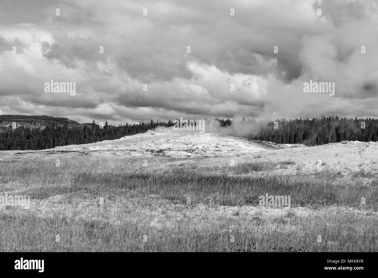 Geyser mound in middle of field steaming, under cloudy sky. Black and white image. - Stock Image