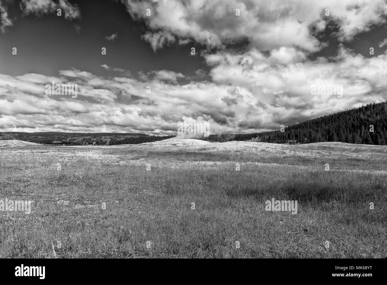 Empty grass field with hills to one side under a cloudy sky, black and white. - Stock Image