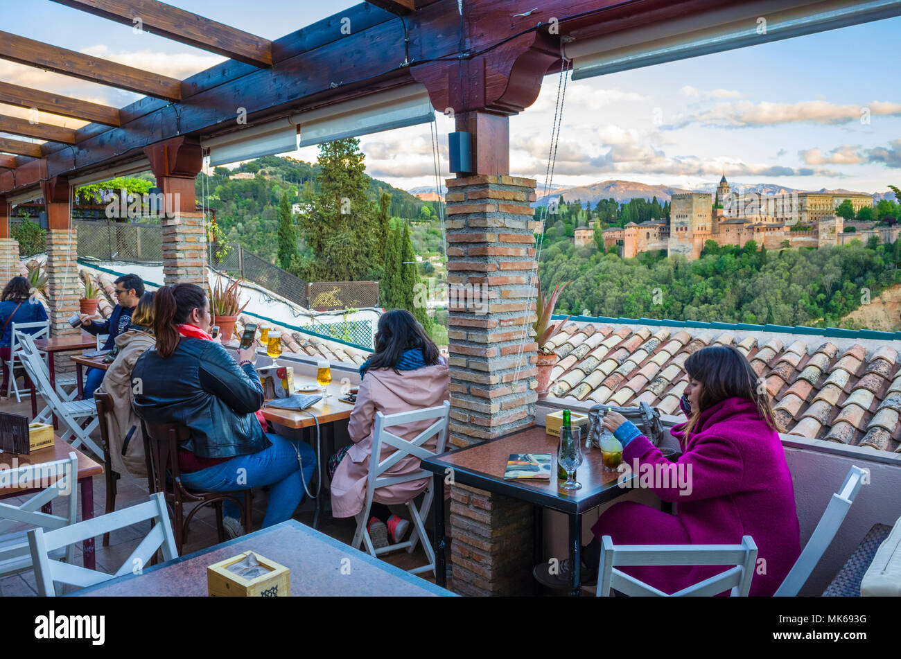 Granada, Spain: Tourists at El Balcón de San Nicolás cafe and restaurant in the Albaicin district old town, enjoy a panoramic view of the Unesco liste - Stock Image