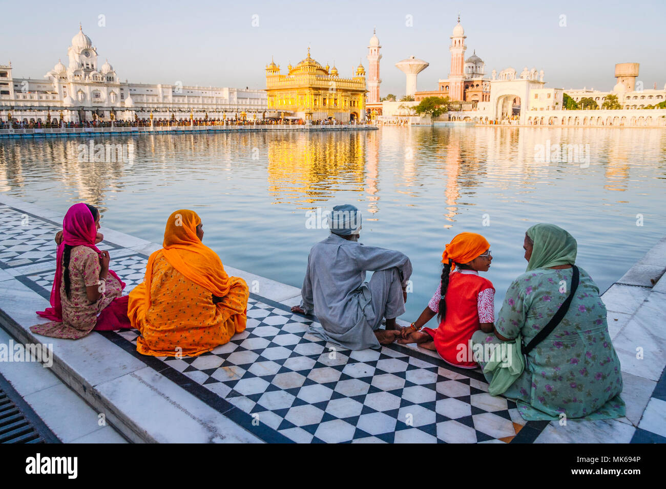 Amritsar, Punjab, India : A Sikh family sits by the pool in the Golden Temple. Stock Photo