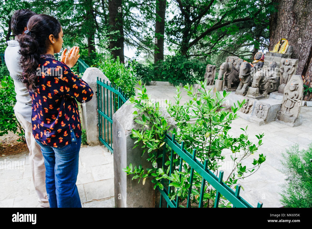 Nagar, Himachal Pradesh, India : Hindu people prays before the ancient stone statue of Guga Chauhan and the guardians of the Kullu valley in the garde - Stock Image