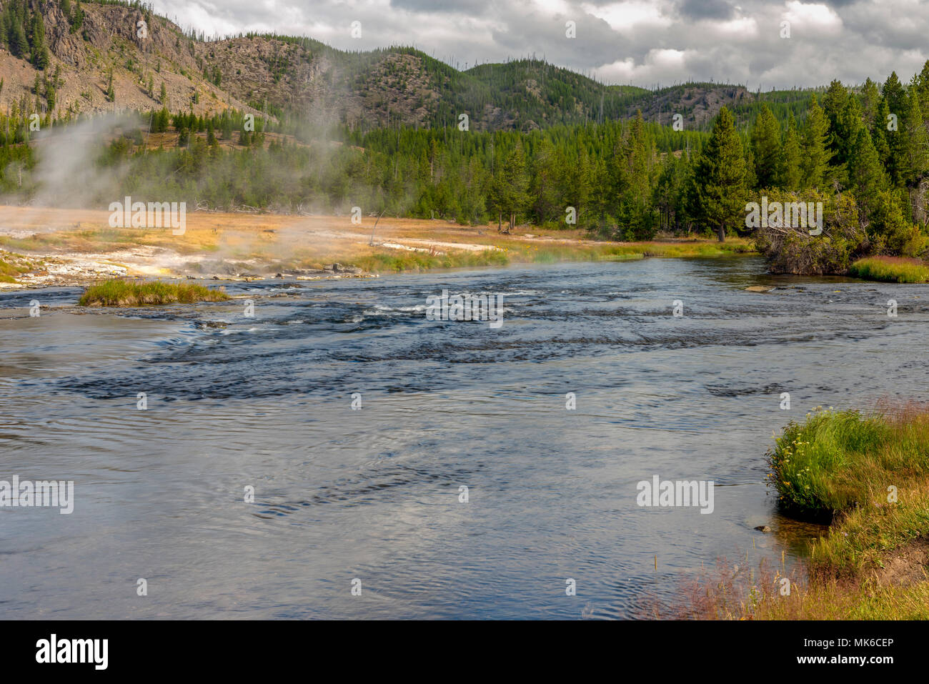 Wide view od slow moving river , meadow and forest under cloudy sky. - Stock Image