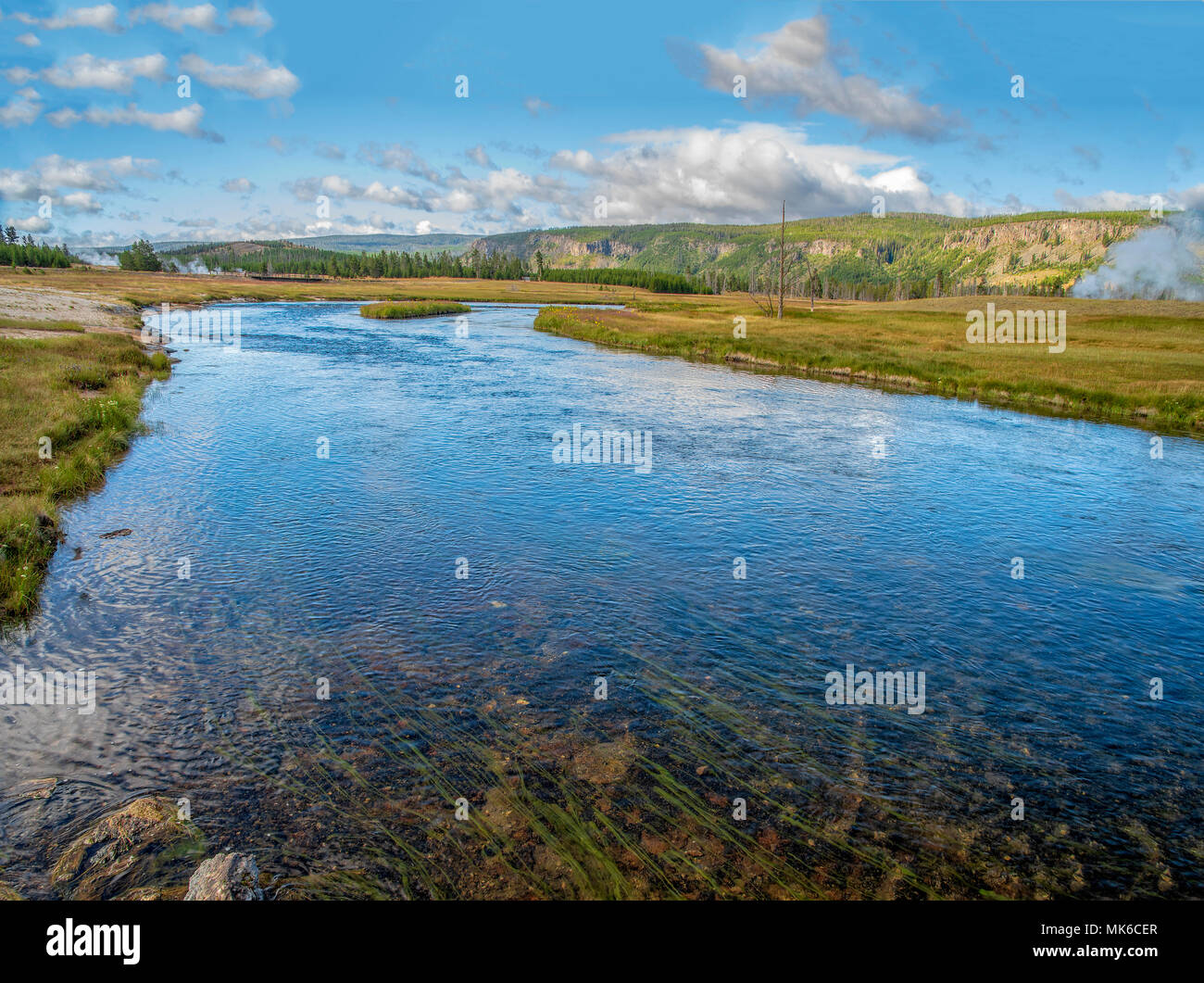 Slow moving river with green meadows heading toward mountains in the background under light blue sky with white fluffy clouds. - Stock Image