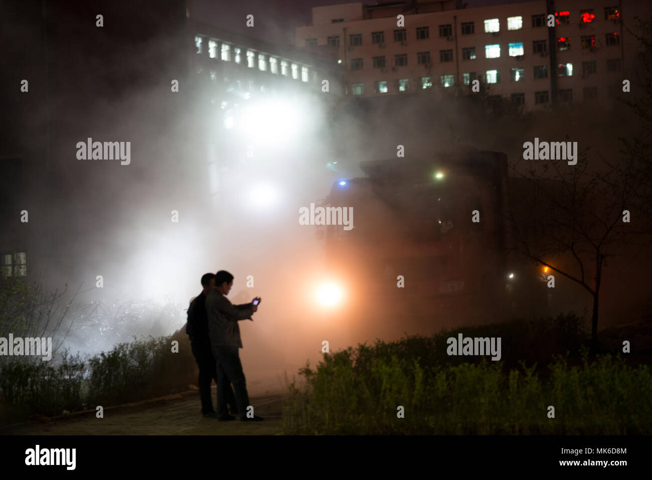 environmental, night, demolish apartments at night, pollution to residents, no-care, 10pm, dust clouds - Stock Image