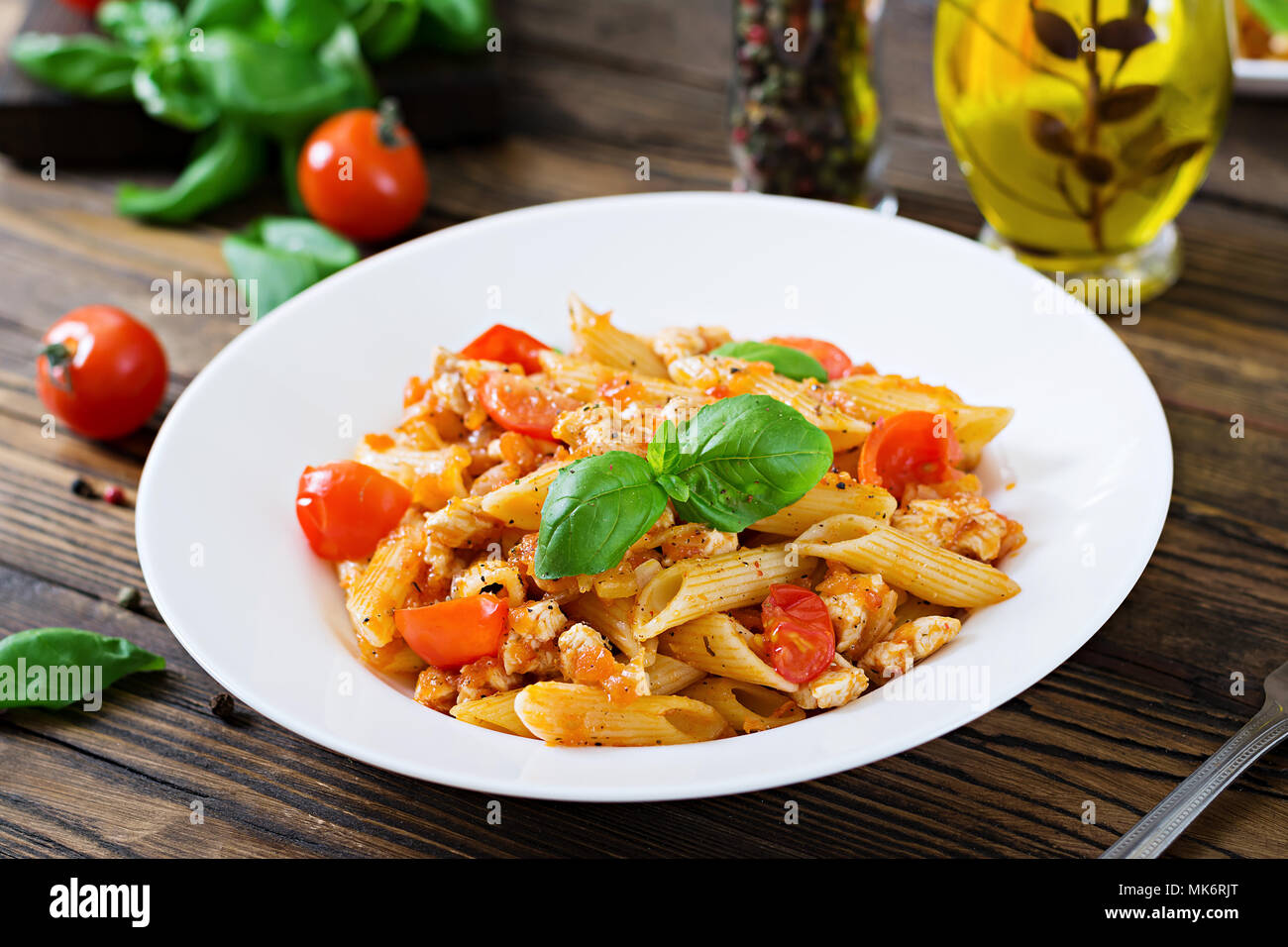 Penne pasta in tomato sauce with chicken, tomatoes, decorated with basil on a wooden table. Italian food. Pasta Bolognese. - Stock Image