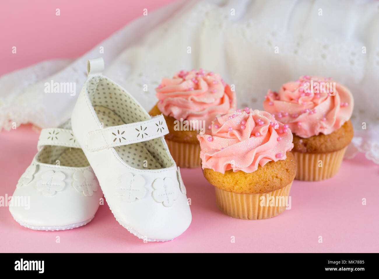 a59c26582f5 Baptism or birthday girl invitation with pink cup cakes and white shoes on pink  background