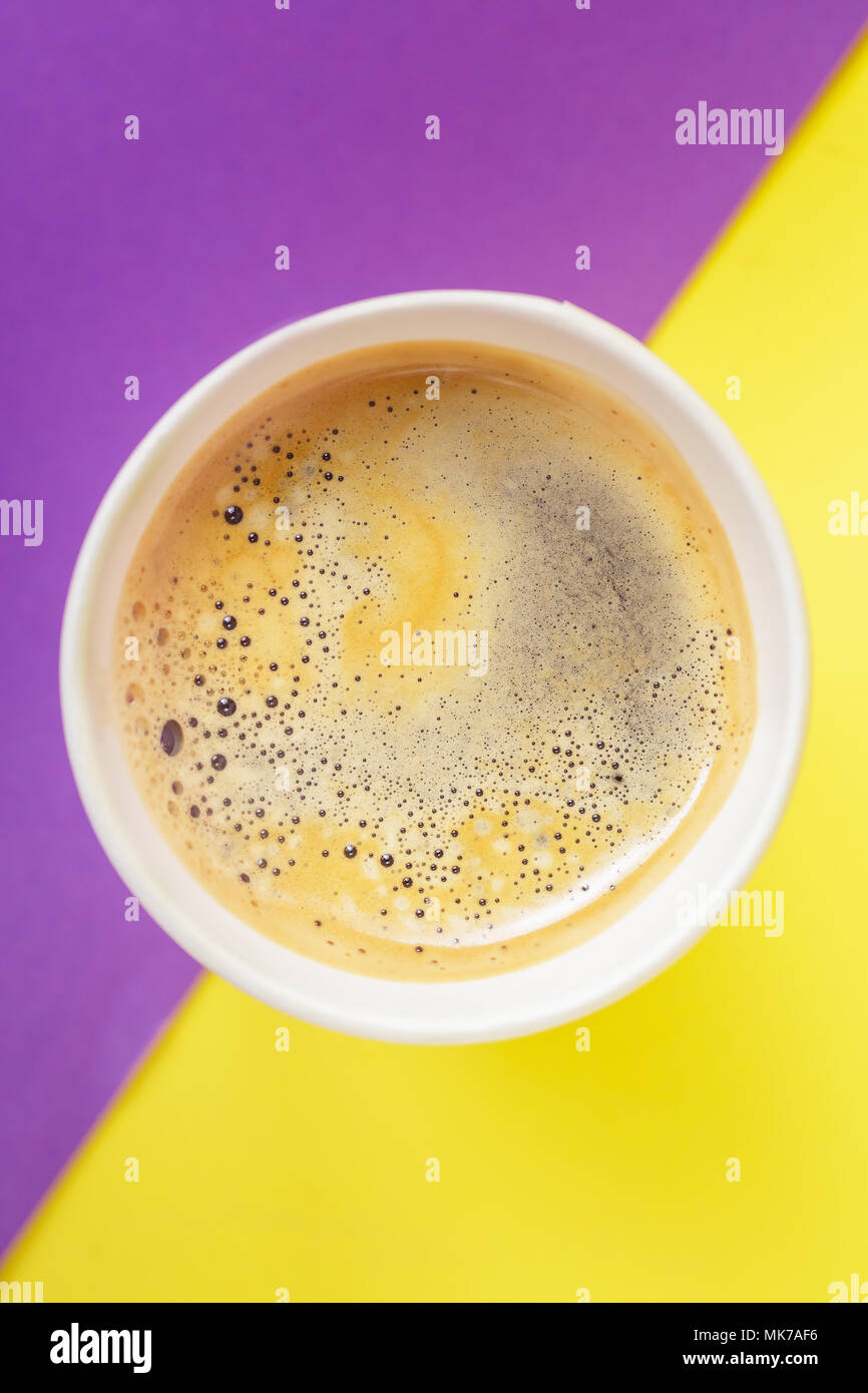 Top view of take-out hot drink in opened thermo cup on vibrant purple and yellow background. Cafe crema foam on the americano coffee Stock Photo