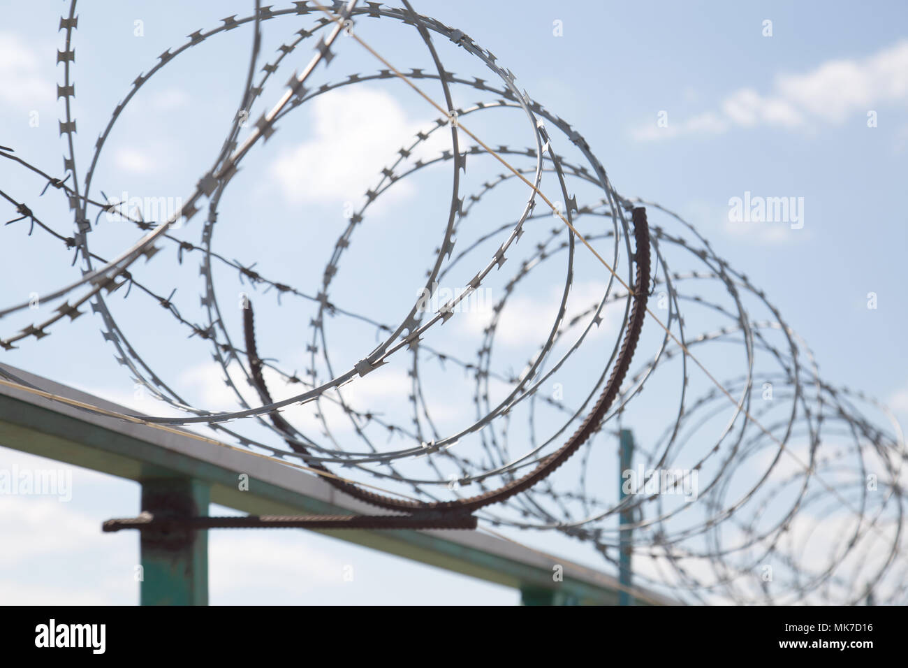 Fence with razor barbed wire protection against blue sky background. Dictatorship and tyranny concept. - Stock Image