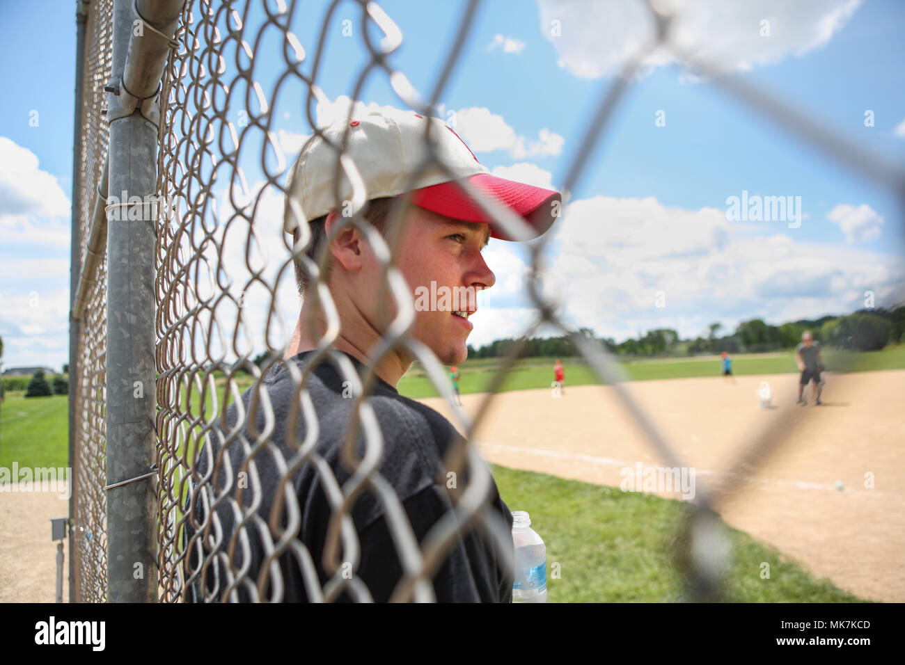 A baseball player photographed through the fence - Stock Image