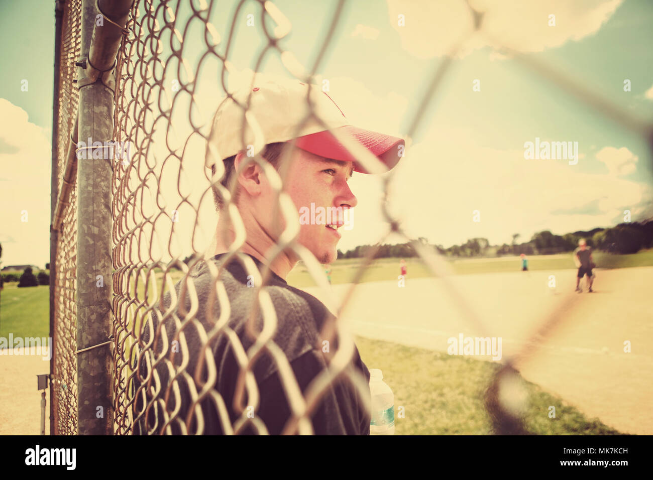baseball player photographed through the fence colorized - Stock Image