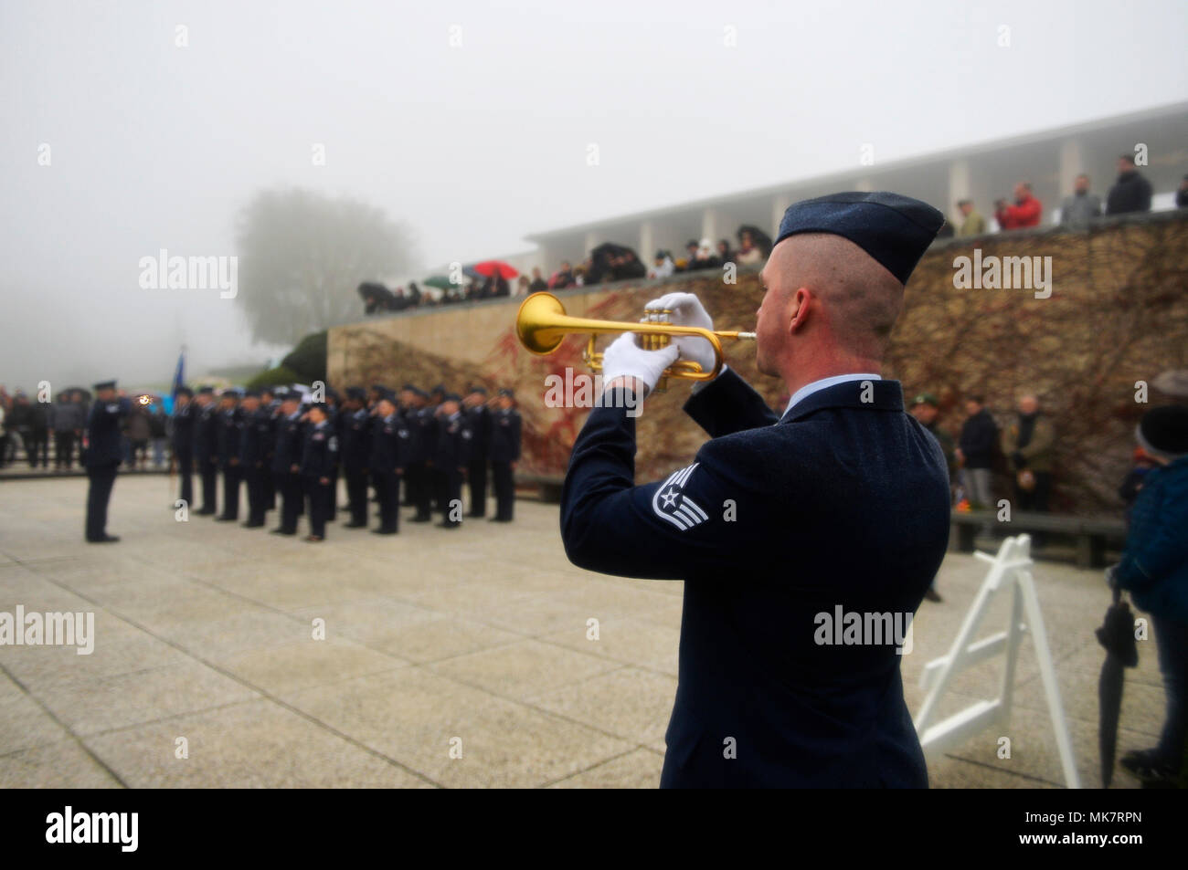 U.S. Air Force Staff Sgt. Ryan Wist, 786th Civil Engineer Squadron water and fuel systems maintenance technician, plays the bugle during a Veterans Day ceremony at Henri-Chapelle American Cemetery and Memorial, Belgium, Nov. 11, 2017. Despite inclement weather, more than 100 veterans and civilians turned up for the ceremony. (U.S. Air Force photo by Airman 1st Class Joshua Magbanua) - Stock Image
