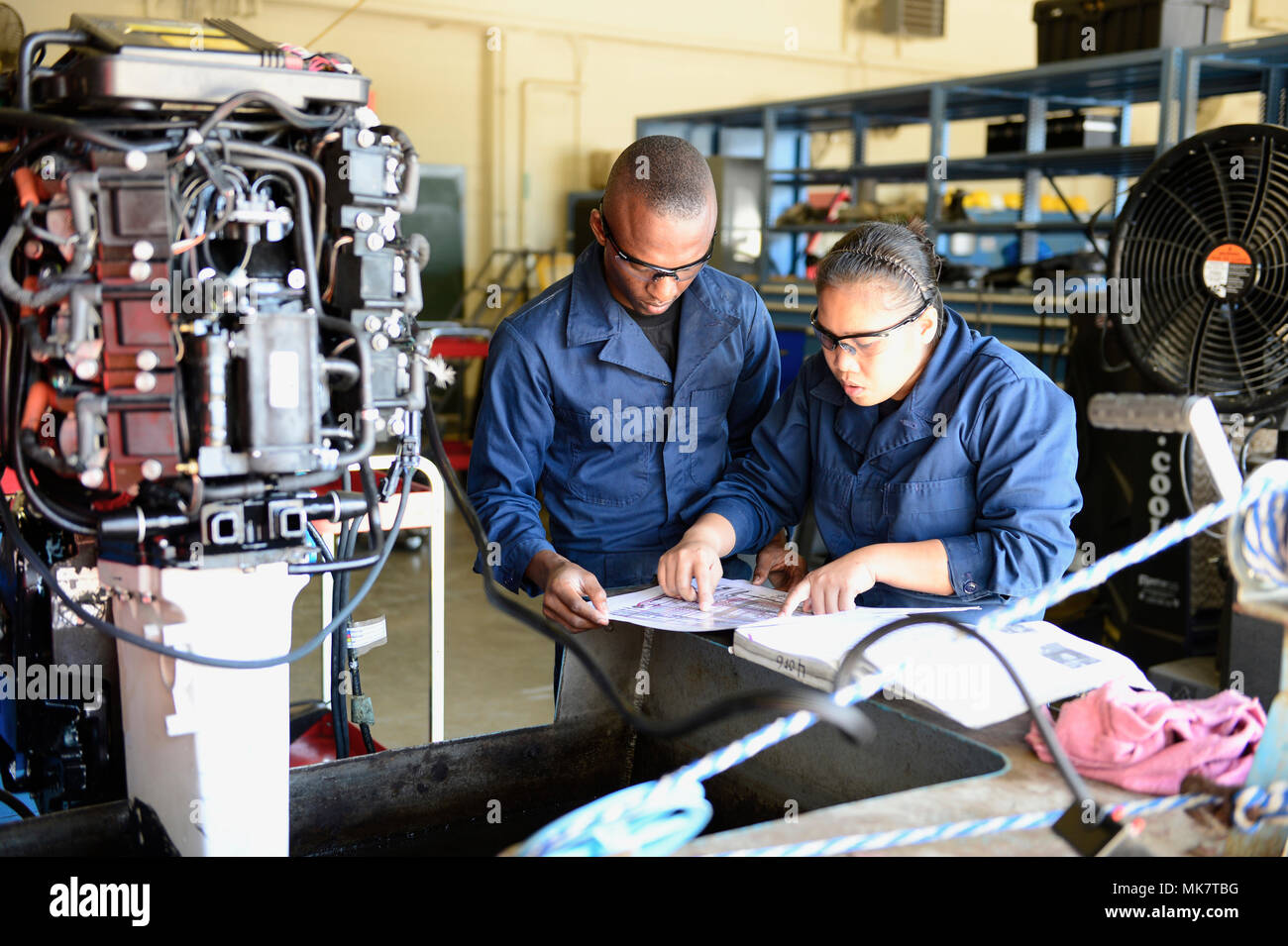 Students go over schematics of an outboard boat engine as part of the Lake Chad Basin Initiative, Nov. 15, 2017 at the Naval Small Craft Instruction and Technical Training School on Stennis Space Center, Miss. NAVSCIATTS is working through the Trans-Sahara Counterterrorism Partnership to facilitate the inaugural iteration of the Lake Chad Basin Initiative. The objective of the iteration is to increase partner nations' abilities to project force against violent extremist organization safe havens within the Lake Chad region using continental United States based maintenance and leadership trainin - Stock Image