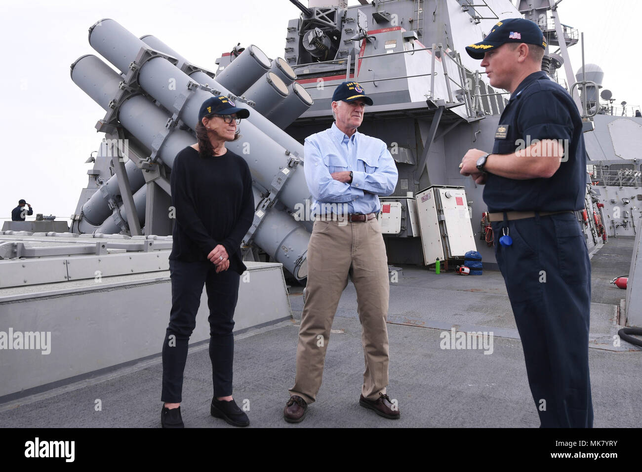 ARABIAN GULF (Nov. 23, 2017) Cmdr. Jeffrey Tamulevich (right), commanding officer of the Arleigh Burke-class guided-missile destroyer USS Hopper (DDG 70), explains the ship's vertical launching system to Secretary of the Navy Richard V. Spencer and his wife, Sarah Pauline Spencer, on Thanksgiving Day. Hopper is deployed to the U.S. 5th Fleet area of operations in support of maritime security operations to reassure allies and partners and preserve the freedom of navigation and the free flow of commerce in the region. (U.S. Navy photo by Mass Communication Specialist 2nd Class Kristina Young/Rel - Stock Image
