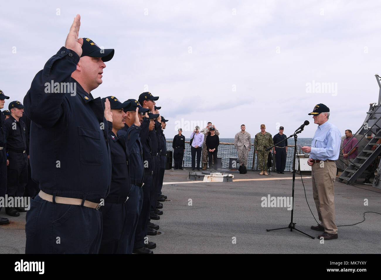 ARABIAN GULF (Nov. 23, 2017) Secretary of the Navy Richard V. Spencer reenlists eight Sailors assigned to the Arleigh Burke-class guided-missile destroyer USS Hopper (DDG 70) during a visit to the ship on Thanksgiving Day. Hopper is deployed to the U.S. 5th Fleet area of operations in support of maritime security operations to reassure allies and partners and preserve the freedom of navigation and the free flow of commerce in the region. (U.S. Navy photo by Mass Communication Specialist 2nd Class Kristina Young/Released) - Stock Image