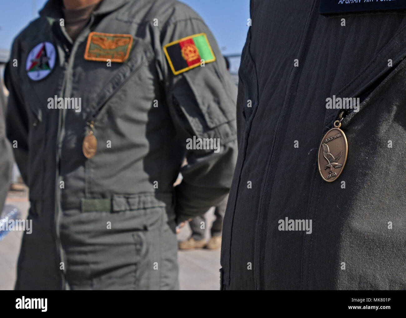 Afghan Air Force pilots wear Black Hawk pendants given by instructors signifying their completion of UH-60 Black Hawk training at Kandahar Airfield, Afghanistan, Nov. 20, 2017. The pilots are the first six to become AAF UH-60 pilots. The pilots have prior experience in the Mi-17 Hip. The transition of airframe for the AAF pilots will provide firepower and mobility, significant offensive factors enabling the Afghan National Defense and Security Forces to break the stalemate with insurgents. (U.S. Air Force photo by Tech. Sgt. Veronica Pierce) - Stock Image