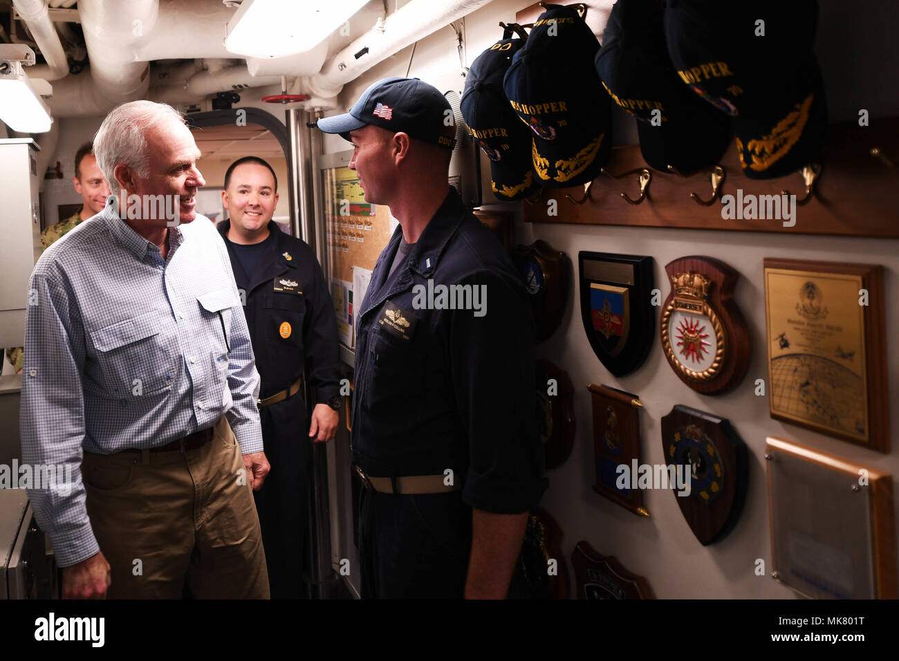 ARABIAN GULF (Nov. 23, 2017) Secretary of the Navy Richard V. Spencer greets Lt. j.g. Keelen Collins, the navigator aboard the Arleigh Burke-class guided-missile destroyer USS Hopper (DDG 70), during a visit to the ship on Thanksgiving Day. Hopper is deployed to the U.S. 5th Fleet area of operations in support of maritime security operations to reassure allies and partners and preserve the freedom of navigation and the free flow of commerce in the region. (U.S. Navy photo by Mass Communication Specialist 2nd Class Kristina Young/Released) - Stock Image