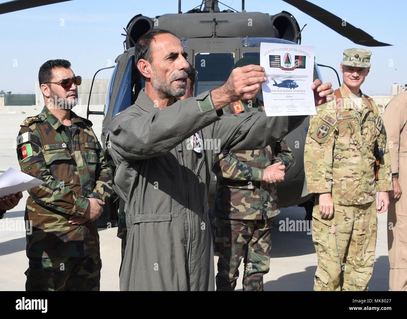 An Afghan Air Force pilot receives a certificate during a UH-60 Black Hawk Aircraft Qualification Training graduation ceremony at Kandahar Airfield, Afghanistan, Nov. 20, 2017. The pilot is one of six to be the first AAF Black Hawk pilots. The first AAF Black Hawk pilots are experienced aviators coming from a Mi-17 background. For future Black Hawk pilots the UH-60 flight training is approximately 16 weeks long, six weeks for Aircraft Qualification Training (AQT) and 10 weeks for Mission Qualification Training (MQT).  (U.S. Air Force photo by Tech. Sgt. Veronica Pierce) - Stock Image