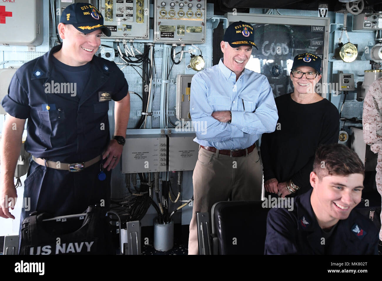ARABIAN GULF (Nov. 23, 2017) From left, Cmdr. Jeffrey Tamulevich, commanding officer of the Arleigh Burke-class guided-missile destroyer USS Hopper (DDG 70), Secretary of the Navy Richard V. Spencer (center), and his wife, Sarah Pauline Spencer, visit with watchstanders in the ship's bridge on Thanksgiving Day. Hopper is deployed to the U.S. 5th Fleet area of operations in support of maritime security operations to reassure allies and partners and preserve the freedom of navigation and the free flow of commerce in the region. (U.S. Navy photo by Mass Communication Specialist 2nd Class Kristina - Stock Image