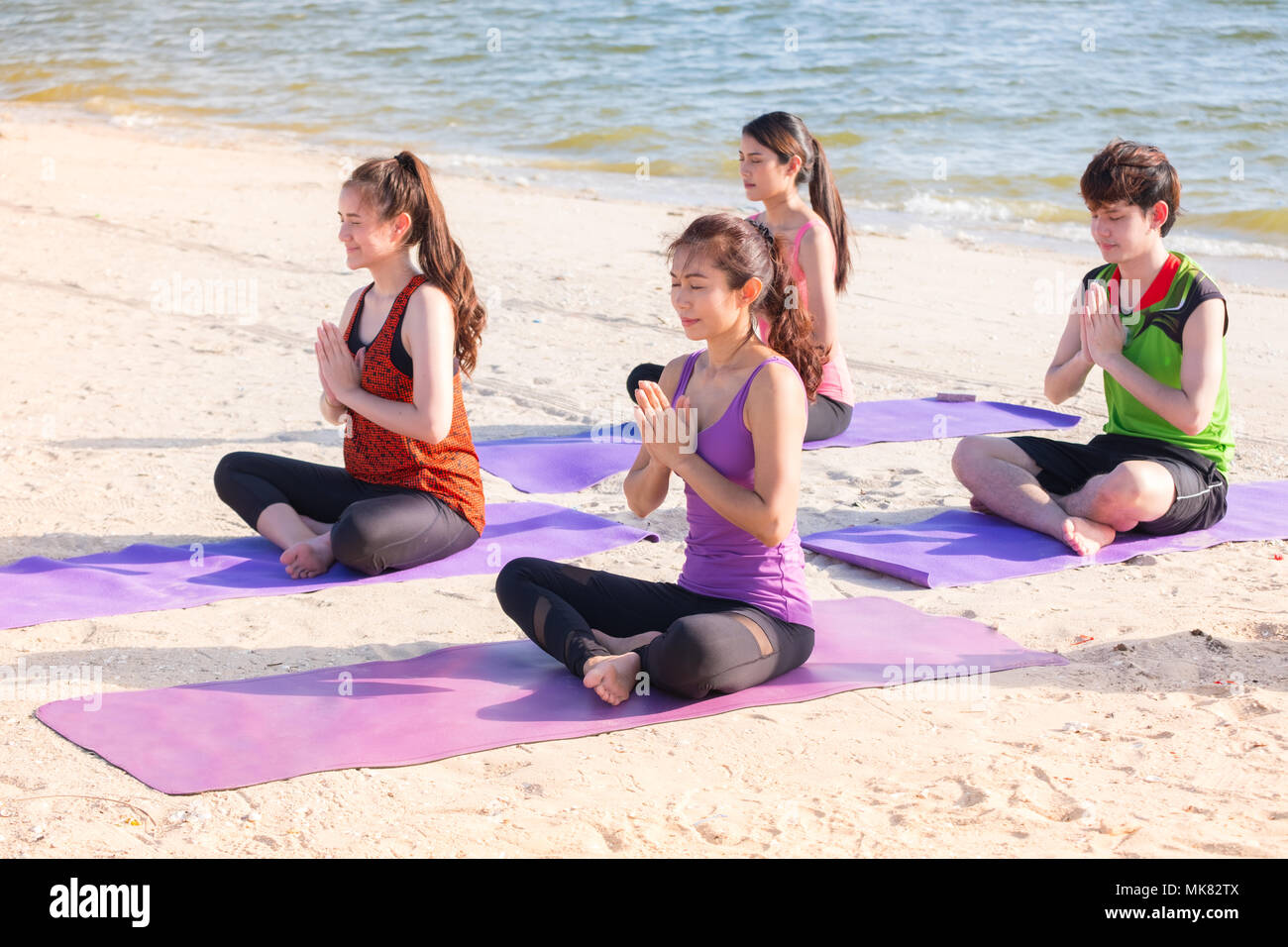 Yoga class at sea beach in sunny day ,Group of people doing namaste pose with clam relax emotion,Meditation pose,Wellness and Healthy balance lifestyl - Stock Image