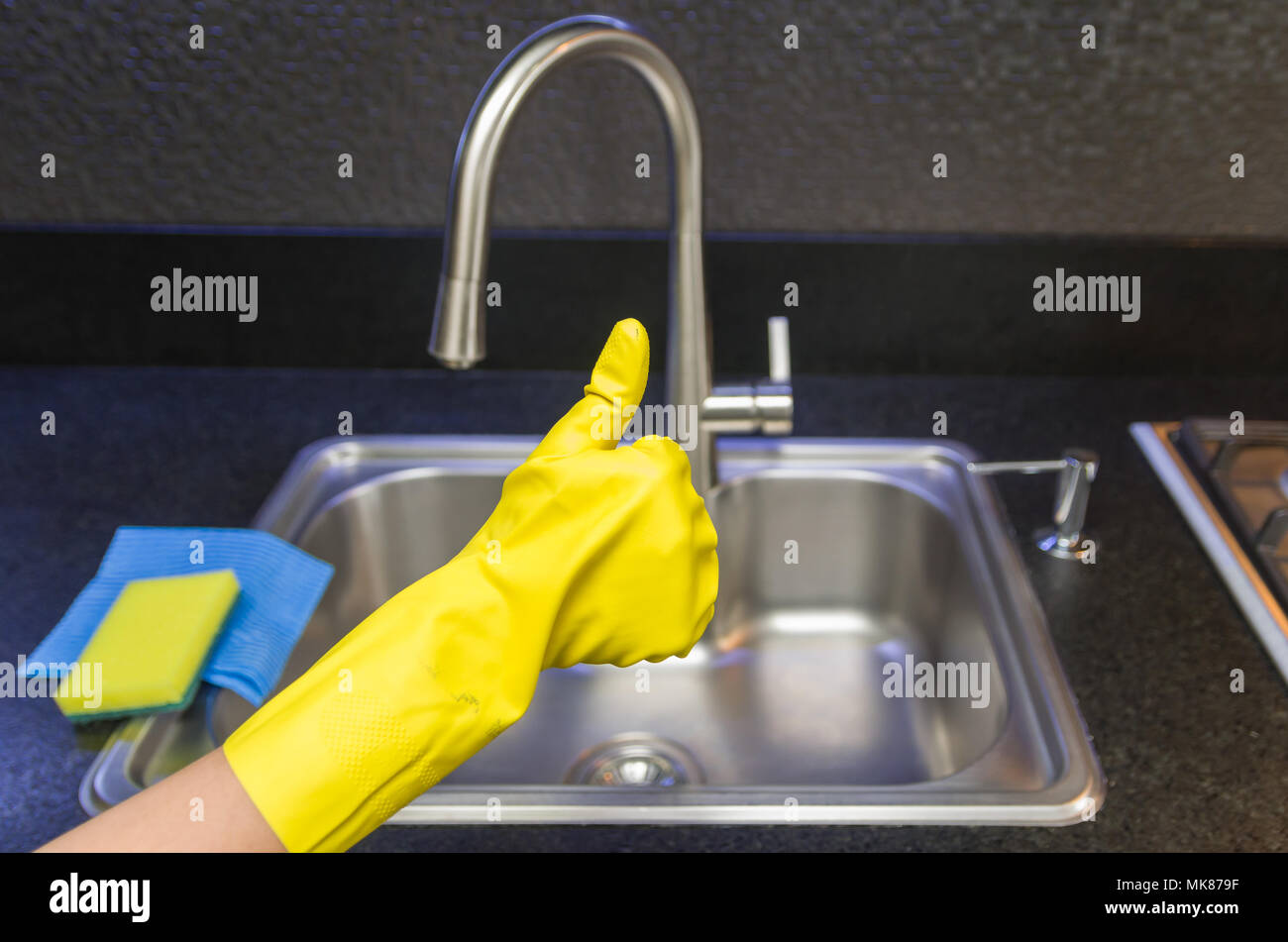 Great concept of domestic cleaning, hand with glove making positive sign with thumb. - Stock Image