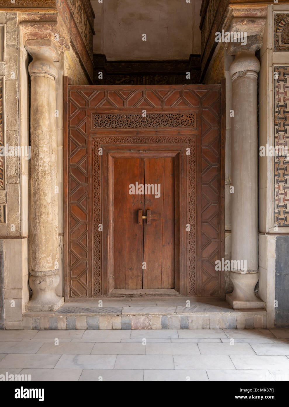 Old wooden door framed by wooden engraved panels decorated with geometric and floral patterns between two carved columns located at Sultan Qalawun Mau - Stock Image