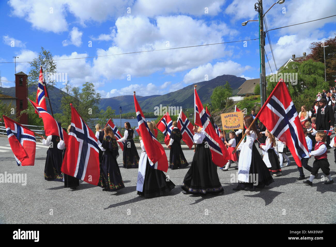 Patriotic Norwegian men and women carry the country flag during a national day parade on 17 May in the town of Vaksdal, in Hordaland County, Norway. Stock Photo