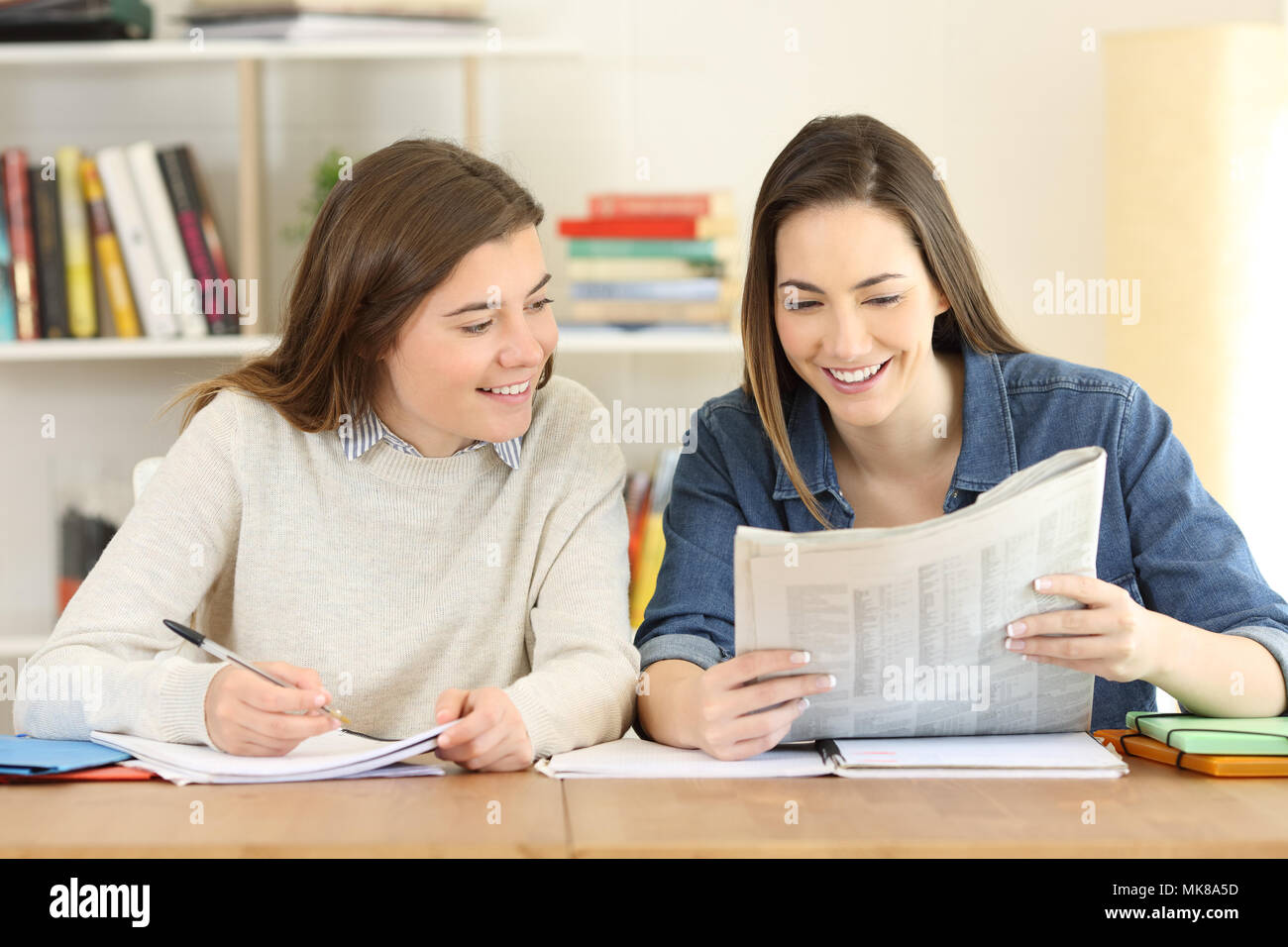 two happy students reading news in a newspaper at home stock photo