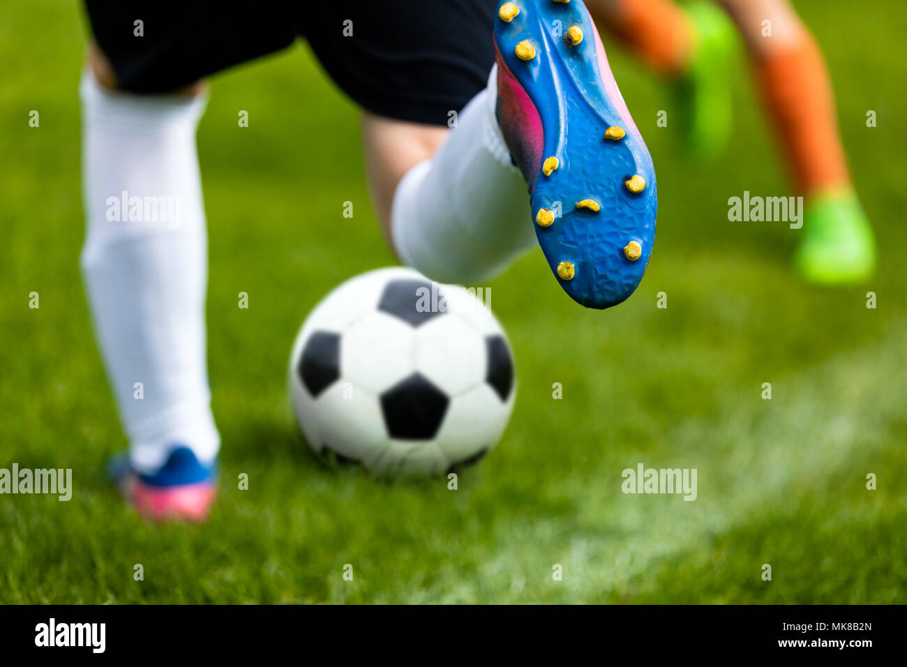 Soccer Kick. Footballer Kicking Ball on Grass Pitch. Football Soccer Player Hits a Ball. Soccer Boots Close Up - Stock Image